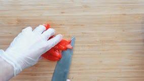 Ciérrese para arriba de un cocinero que corta un paprika rojo en una tabla de cortar de madera Visión superior almacen de video
