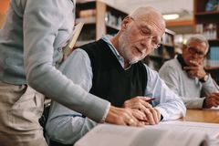 Ciérrese para arriba de un conferenciante que dirige a un estudiante mayor en sala de clase foto de archivo