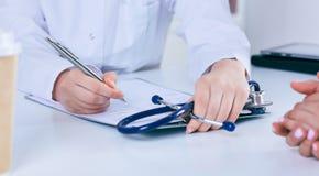 Ciérrese para arriba de un doctor de sexo femenino que llena encima de un formulario de inscripción mientras que consulta al paci foto de archivo libre de regalías