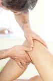 Ciérrese para arriba de un fisio dando masajes a una pierna Foto de archivo libre de regalías