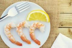 Ciérrese para arriba de un grupo de camarones y de un limón servido en un pla blanco Imágenes de archivo libres de regalías