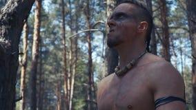 Ciérrese para arriba de un guerrero antiguo con la pintura de la cara negra en su cara, en el bosque almacen de metraje de vídeo