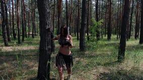 Ciérrese para arriba de un guerrero femenino con una espada en el bosque, 4k metrajes
