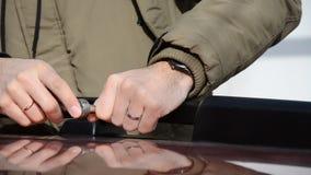 Ciérrese para arriba de un hombre de mediana edad en abrigo esquimal sujeta los tornillos en el estante de la verja del coche con almacen de metraje de vídeo