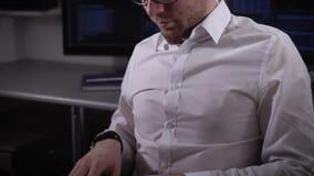 Ciérrese para arriba de un hombre de negocios joven que trabaja en el ordenador portátil El especialista de las TIC de la compañí almacen de video