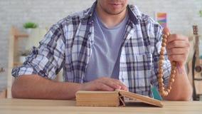 Ciérrese para arriba de un hombre joven con un rosario en sus manos, leyendo la biblia almacen de metraje de vídeo