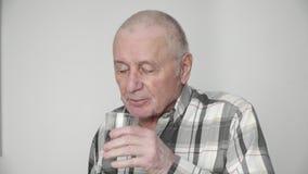 Ciérrese para arriba de un hombre mayor consigue su píldora en casa 4k almacen de metraje de vídeo
