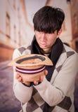Ciérrese para arriba de un hombre medio joven sin hogar triste, con un sombrero en sus manos, pidiendo dinero, en un fondo borros foto de archivo