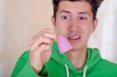 Ciérrese para arriba de un hombre que hace una cara repugnante mientras que está sosteniendo una taza menstrual en sus manos, en  Fotografía de archivo