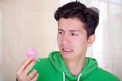 Ciérrese para arriba de un hombre que hace una cara repugnante mientras que está sosteniendo una taza menstrual en sus manos, en  Imágenes de archivo libres de regalías