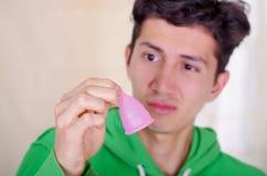 Ciérrese para arriba de un hombre que hace una cara repugnante mientras que está sosteniendo una taza menstrual en sus manos, en  Imagen de archivo libre de regalías