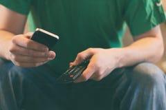 Ciérrese para arriba de un hombre que sostiene un teléfono celular y una TV teledirigidos Imagen de archivo libre de regalías