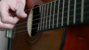 Ciérrese para arriba de un hombre que toca una guitarra acústica almacen de video