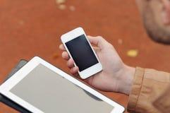 Ciérrese para arriba de un hombre que usa el dispositivo de la tableta y del teléfono, tecnología concentrada Fotos de archivo libres de regalías