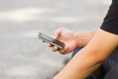 Ciérrese para arriba de un hombre que usa el teléfono elegante móvil Imagen de archivo libre de regalías
