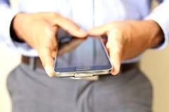 Ciérrese para arriba de un hombre que usa el teléfono elegante móvil fotografía de archivo libre de regalías