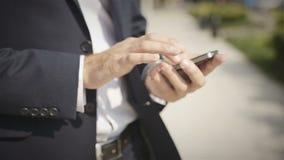 Ciérrese para arriba de un hombre que usa el teléfono elegante móvil al aire libre metrajes