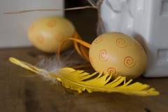 Ciérrese para arriba de un huevo amarillo con la pluma, día de fiesta de Pascua foto de archivo libre de regalías