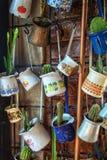 Ciérrese para arriba de un manojo de diversos potes del jezve del café colgados encima como de decoración en un café foto de archivo