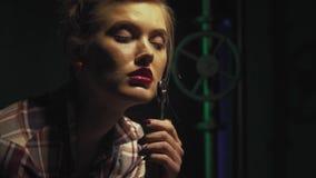 Ciérrese para arriba de un mecánico de sexo femenino que se sienta con una llave, tubos en el fondo almacen de metraje de vídeo