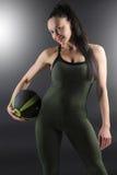 Ciérrese para arriba de un modelo femenino hermoso de la aptitud que sostiene una bola del gimnasio en su lado Imágenes de archivo libres de regalías