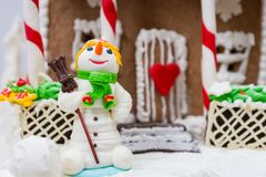Ciérrese para arriba de un muñeco de nieve de la masilla del azúcar cerca de casa de pan de jengibre Fotos de archivo