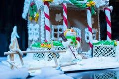 Ciérrese para arriba de un muñeco de nieve de la masilla del azúcar cerca de la casa de pan de jengibre a Fotografía de archivo libre de regalías