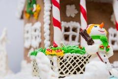 Ciérrese para arriba de un muñeco de nieve de la masilla del azúcar cerca de hou grande del pan de jengibre Fotografía de archivo libre de regalías