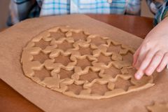 Ciérrese para arriba de un niño pequeño que toma una galleta en la cocina mientras que sus padres están cocinando Pan de jengibre foto de archivo