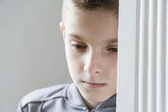 Ciérrese para arriba de un niño presionado en chaqueta gris Imagenes de archivo