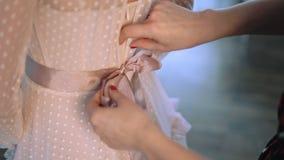 Ciérrese para arriba de un nudo en la correa de un vestido color de rosa para las mujeres metrajes