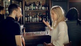 Ciérrese para arriba de un par cariñoso que tiene fecha en el restaurante Hombre joven y mujer hermosa que hablan el uno al otro  metrajes
