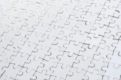 Ciérrese para arriba de un rompecabezas blanco en estado montado en perspectiva Muchos componentes de un mosaico entero grande se fotos de archivo