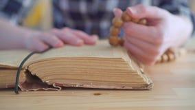 Ciérrese para arriba de un rosario en las manos de una mujer y de la biblia abierta metrajes