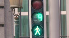 Ciérrese para arriba de un semáforo, con los números contando abajo y un hombre que camina