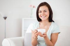 Ciérrese para arriba de un té de consumición de la mujer dark-haired Foto de archivo libre de regalías