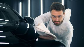 Ciérrese para arriba de un técnico de sexo masculino que pule un automóvil almacen de metraje de vídeo