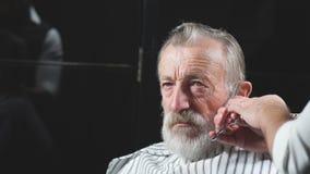 Ciérrese para arriba de un trabajo del peluquero s para un viejo hombre hermoso en la peluquería de caballeros metrajes