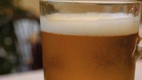 Ciérrese para arriba de un vidrio de cerveza puesto en una tabla almacen de metraje de vídeo