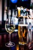 Ciérrese para arriba de un vidrio de vino y de una cerveza foto de archivo