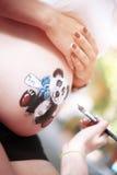 Ciérrese para arriba de un vientre embarazada lindo con el oso Fotos de archivo libres de regalías