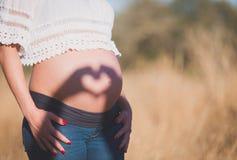 Ciérrese para arriba de un vientre embarazada lindo Cortina bajo la forma de corazón T Imágenes de archivo libres de regalías