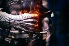 Ciérrese para arriba de una armadura de acero medieval con la mano del guante del hierro que estalla con las llamas del fuego imágenes de archivo libres de regalías