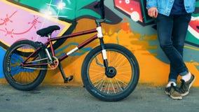Ciérrese para arriba de una bici de BMX y de las piernas del varón que se colocan al lado de ella almacen de video