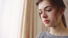 Ciérrese para arriba de una cara de la mujer joven hermosa con los ojos azules que llevan el suéter casual gris almacen de metraje de vídeo