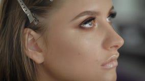Ciérrese para arriba de una cara del photomodel femenino profesional joven durante proceso del maquillaje en la tienda de belleza almacen de video