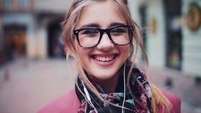 Ciérrese para arriba de una cara femenina tímida joven que sonríe feliz hacia la cámara Emociones verdaderas Sensaciones felices  metrajes