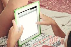 Ciérrese para arriba de una chica joven con la tableta en las manos que mienten encendido Imágenes de archivo libres de regalías