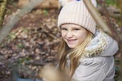 Ciérrese para arriba de una chica joven que se sienta en una madera, visión elevada Imagen de archivo libre de regalías