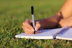Ciérrese para arriba de una escritura de la mano de la mujer en un cuaderno al aire libre Foto de archivo libre de regalías